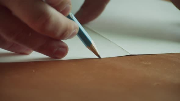 The Process of Creating an Original Handmade Leather Product By a Tanner. Pencil and Pattern Close