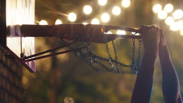 Cover Image for Basketball Ball Getting in the Hoop on Playground at Night - Slam Dunk