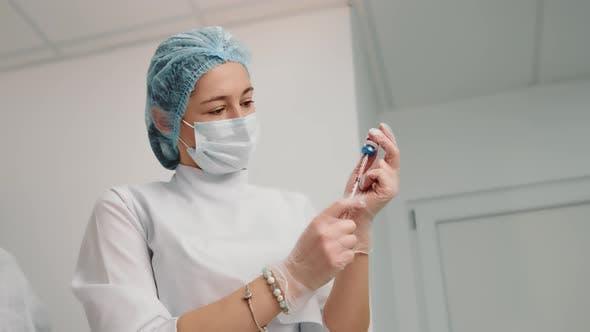 Nurse Typing the Drug Into a Syringe