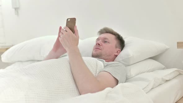 Thumbnail for Man Using Smart Phone in Bed