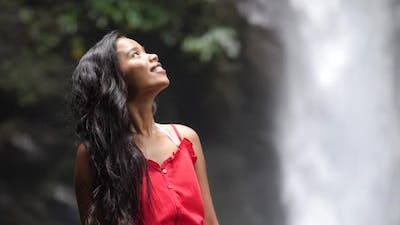 Half Body Shot of Young and Smiling Woman with Unfocused Waterfall Background.