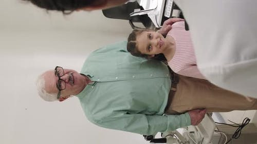 Little Girl With Granddad At Oculist Appointment