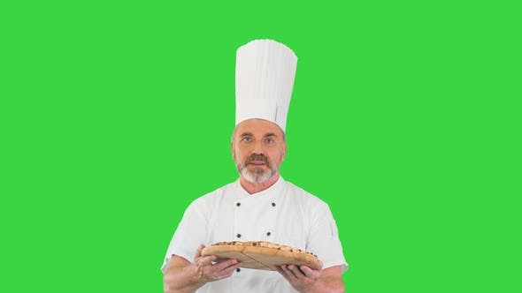 Thumbnail for Attractive Cook with a Pizza in Hands Walking and Talking To Camera on a Green Screen, Chroma Key.