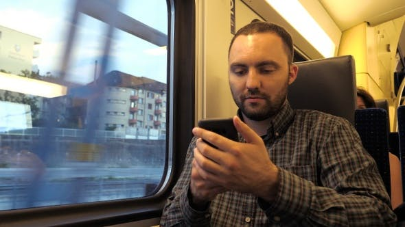 Thumbnail for Young man using smartphones in the subway.