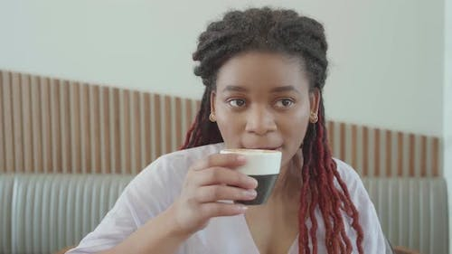 Attractive Young African Woman Drinking Cappuccino in Cafe
