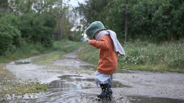 Thumbnail for Game Outdoor, Little Kid Male in Hat and Rubber Boots Plays in Puddle Outdoors