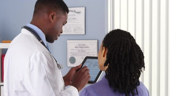 Thumbnail for African American doctor taking patient history with tablet computer