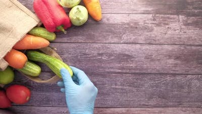 Hand in Gloves Taking Vegetable Out From a Reusable Bag Vegetables Top View