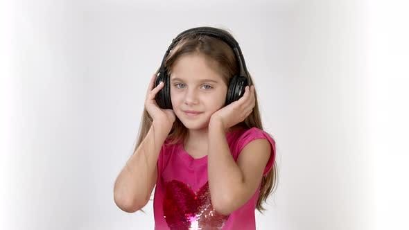 Thumbnail for Happy Emotions of a Little Girl in a Bright Pink Dress. A Little Girl with Headphones Dancing and
