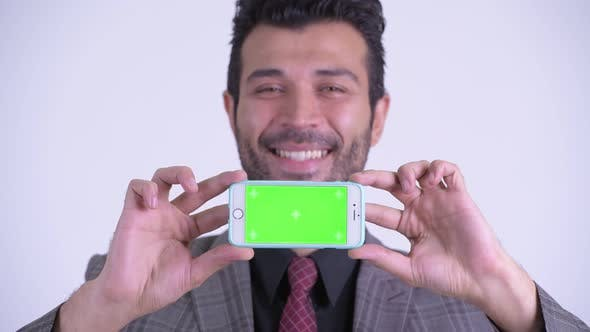 Thumbnail for Face of Happy Bearded Persian Businessman Showing Phone
