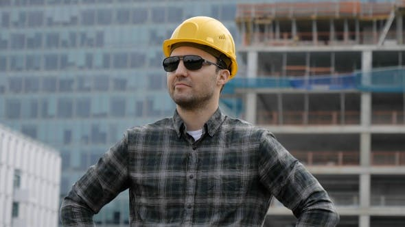 Builder caucasian in a helmet and sunglasses against the