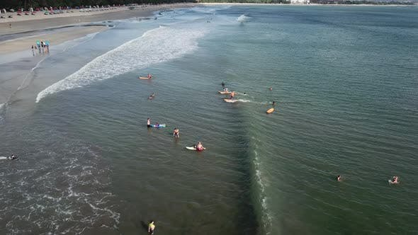 Surfers By the Coast Ride on the Foam