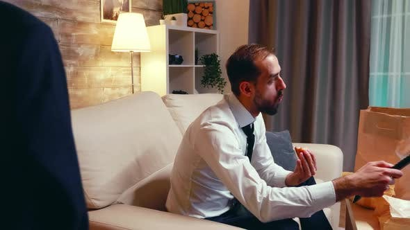 Side View of Businessman Eating Junk Food and Drinking Beer