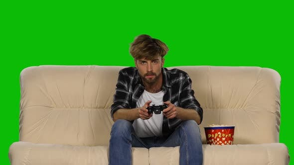 Thumbnail for Gamer Is Playing with a Joystick While Eating Popcorn. Green Screen