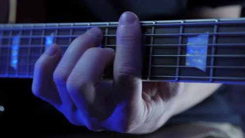 Close up of male hand playing on guitar strings, learning new chords