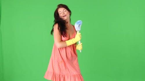 Niedliche junge Frau tanzen mit Toilettenbürste und Schwamm