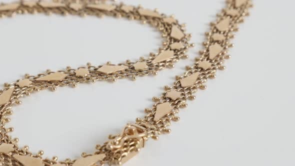 Thumbnail for Complex structure of golden necklace 4K tilting footage