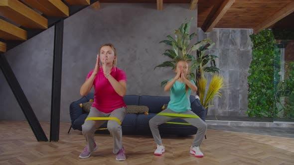 Sportlich Fit Mama und Kind machen Banded Squat Drinnen