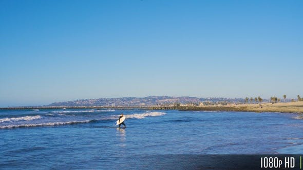 Surfer Guy with Surfboard Walking out of Water Towards Beach