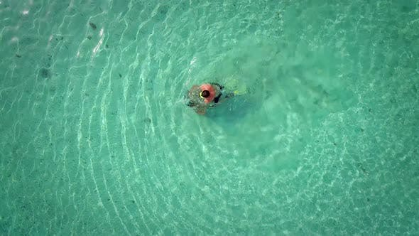 Thumbnail for Aerial view of man and woman playing in turquoise sea.