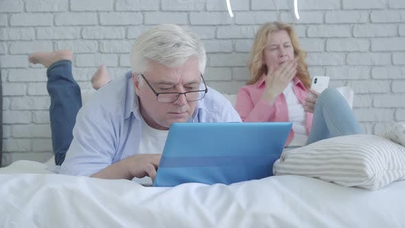 Portrait of Absorbed Caucasian Mid-adult Man Using Laptop As Blurred Woman with Smartphone Sitting