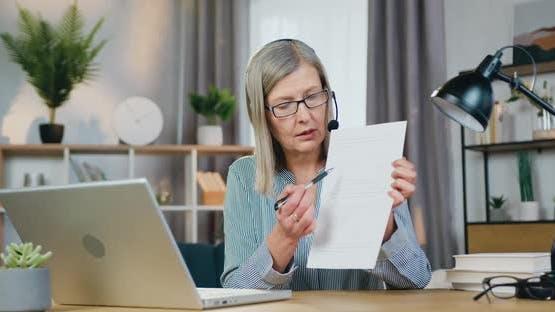 Aged Female Teacher Leading Online Lesson Using Laptop