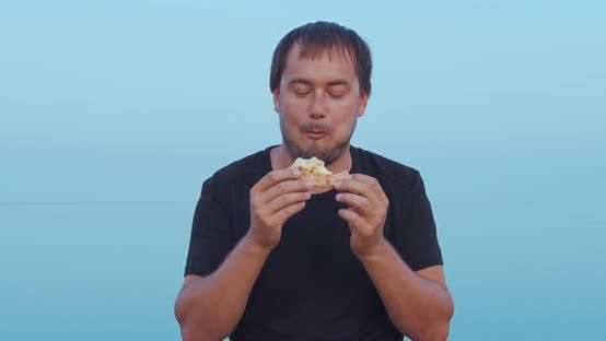 Thumbnail for The Man Sitting and Eat Pizza Outdoor