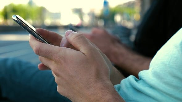 Thumbnail for Men using their mobile phones sitting on a bench.