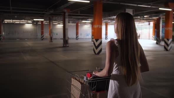 Thumbnail for Woman Walking with Shopping Cart Through Parking