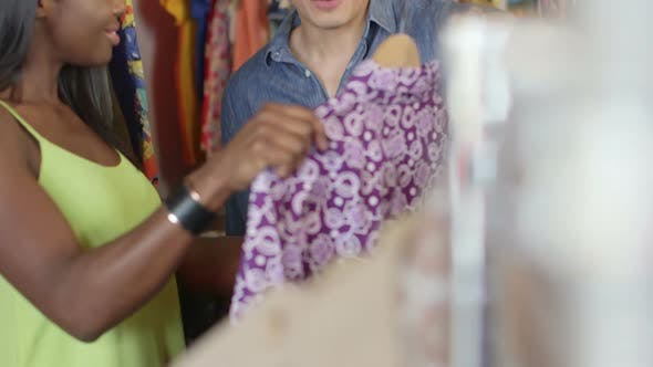 Thumbnail for A Young Man and a Young Woman browse through a rack of colourful vintage clothing in a store