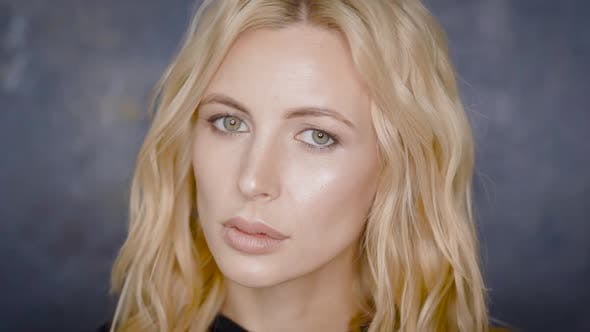 Thumbnail for Porträt eines Blondes Modell posiert gegen graue Wand