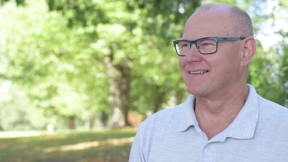 Thumbnail for Happy Senior Man Smiling While Thinking At The Park