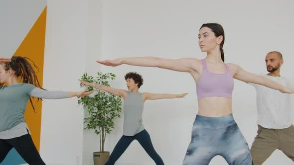 Slow Motion of Group of People Doing Yoga in Light Room Enjoying Execises