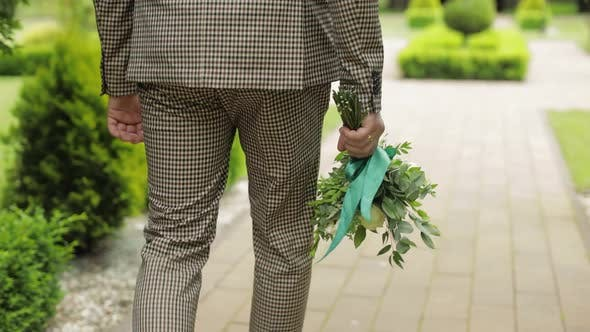 Thumbnail for Groom Goes Down the Alley Between Bushes with a Wedding Bouquet To His Beloved Bride