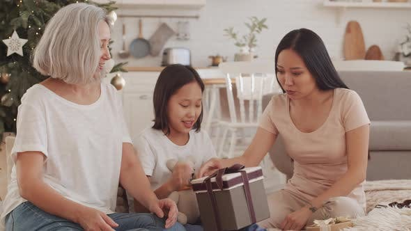 Thumbnail for Happy Asian Family Sharing Christmas Gifts at Home