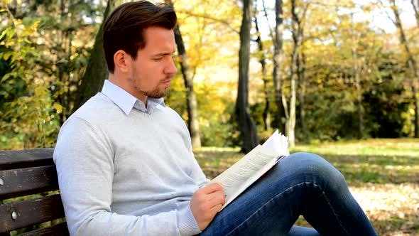 Thumbnail for Young Man Sits on Bench in a Park and with Interest Reads a Book