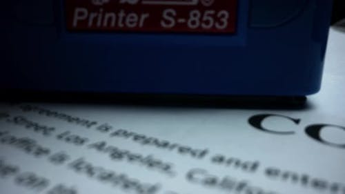 Rubber Stamp Making Seal on Contract, Red Stamp with Text Approved on Document