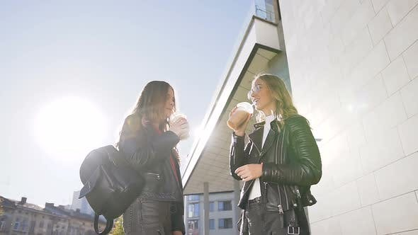 Cover Image for Girls Drinking of Cold Fresh Juice While Walking Outdoors on Sunny Warm Day