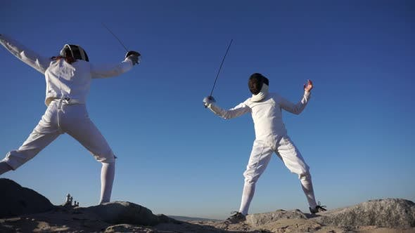 Thumbnail for A man and woman fencing on the beach