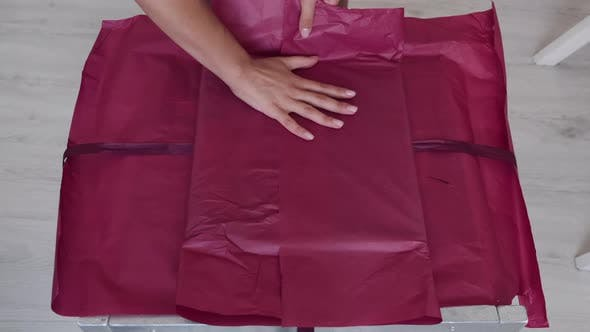 Thumbnail for Closeup of Female Hands Wrapping Gift with Pink Paper