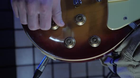 Turning volume and tone knobs on electric guitar