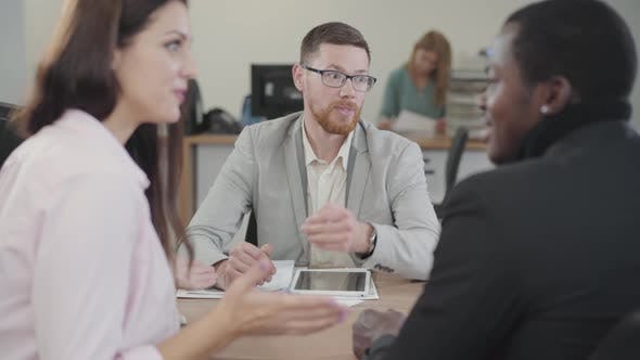 Cover Image for Portrait of Redhead Caucasian Salesman in Eyeglasses Talking To Excited Multiracial Couple in