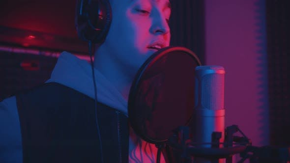 Thumbnail for A Man in Hoodie Rapping Through the Pop-filter in the Microphone - Sound Recording Studio