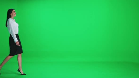 Young Businesswoman in a Suit Walks on a Green Background Chroma Key Template