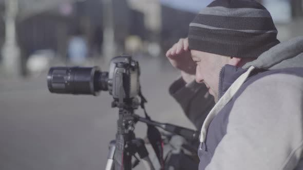 Thumbnail for Man Male Cameraman Photographer with a Camera DSLR on a Tripod in the City Shoots Video Photo . Kyiv