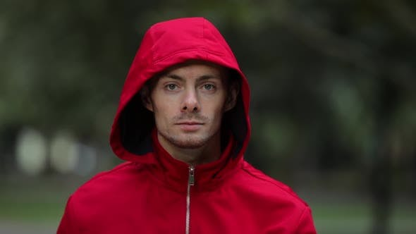 Thumbnail for Man Under Colorful Red Hood Turning Face and Looking at Camera