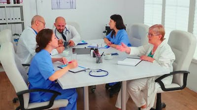 Medical Expert Talking with Medical Staff During Healthcare Meeting