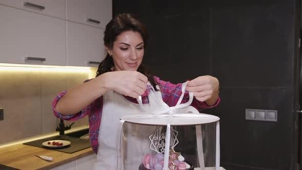 Thumbnail for Weibliche Köchin wickelt einen Geburtstagskuchen in einer transparenten Box mit Klebebändern ein