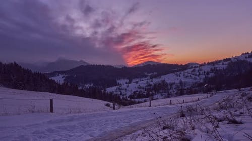 Winter snowy frosty landscape with fence, colorful moving red clouds ,, dusk over snowy landscape,