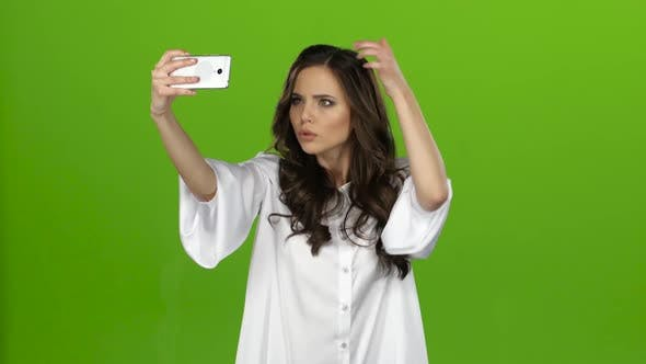 Thumbnail for Girl of with a Smartphone in Her Hands Makes Selfie. Green Screen